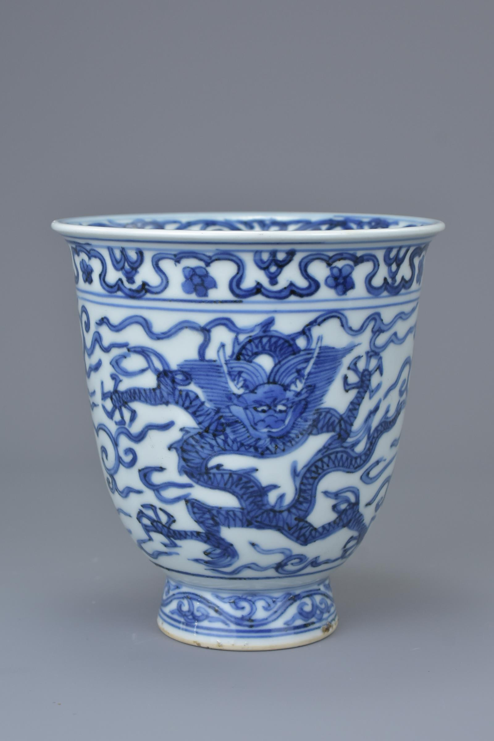 Lot 27 - A Chinese Ming Dynasty or later blue and white porcelain dragon beaker