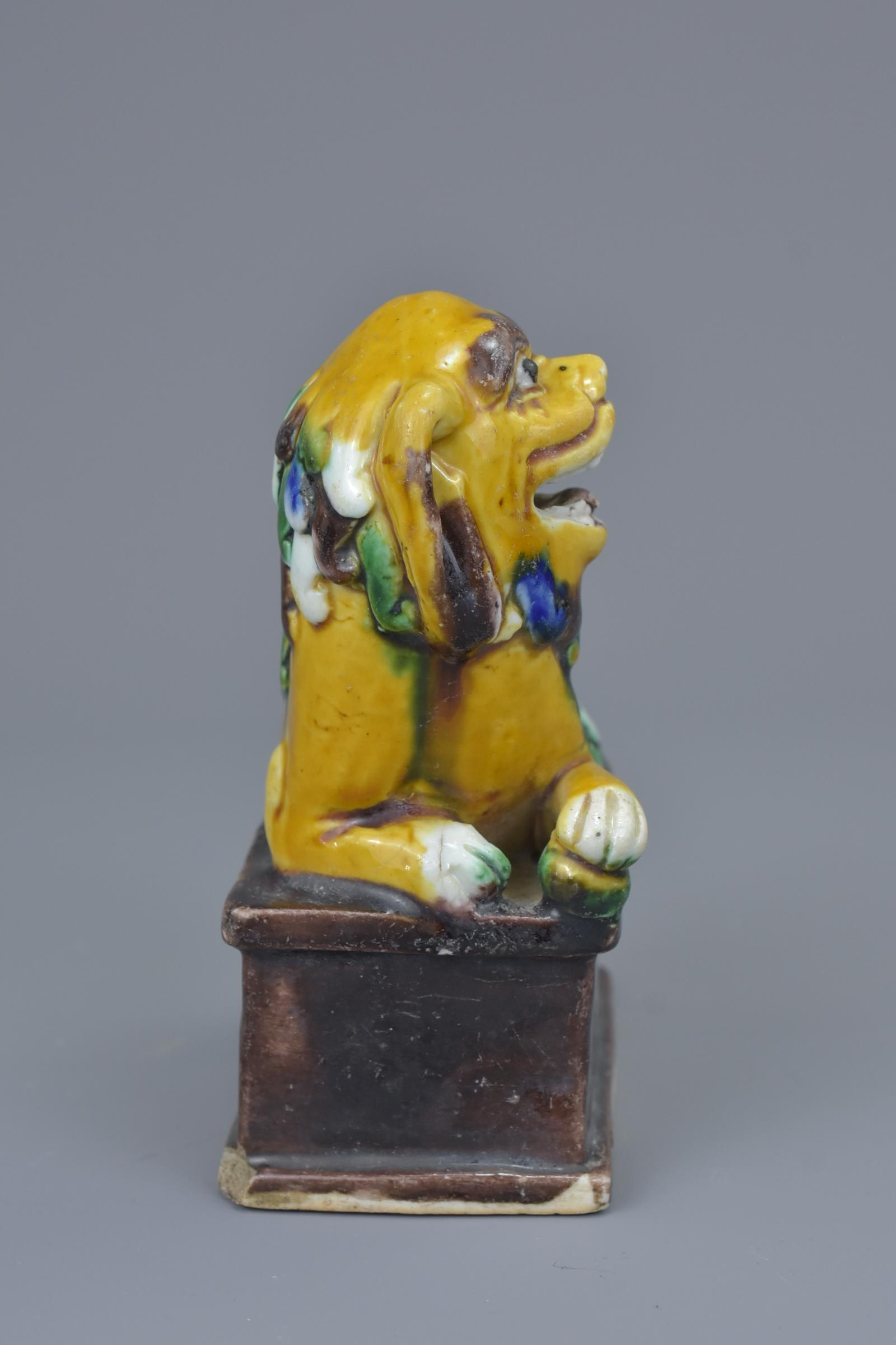 Lot 36 - A Chinese 19/20th C. sancai biscuit porcelain figure of a Foo Dog