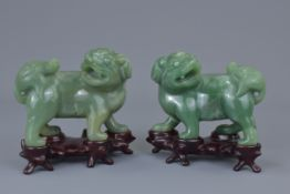 A pair of Chinese 19th C. carved jade lions on wooden stands