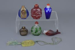 A group of six Chinese carved glass snuff bottles and jade pendant