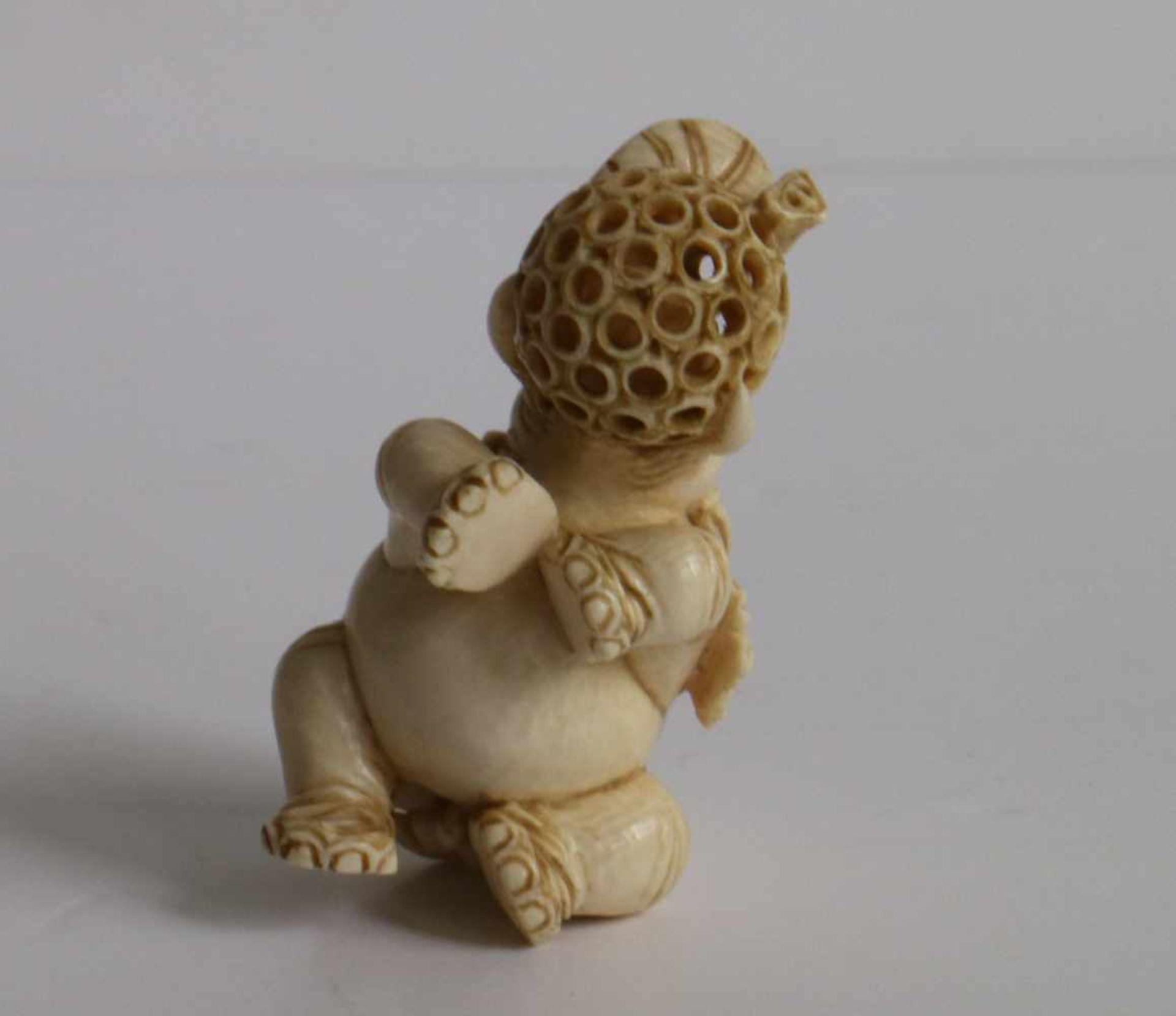 Los 481 - Carved ivory netsuke of an elephant holding a puzzle ball with loose carved inner ball Japan,
