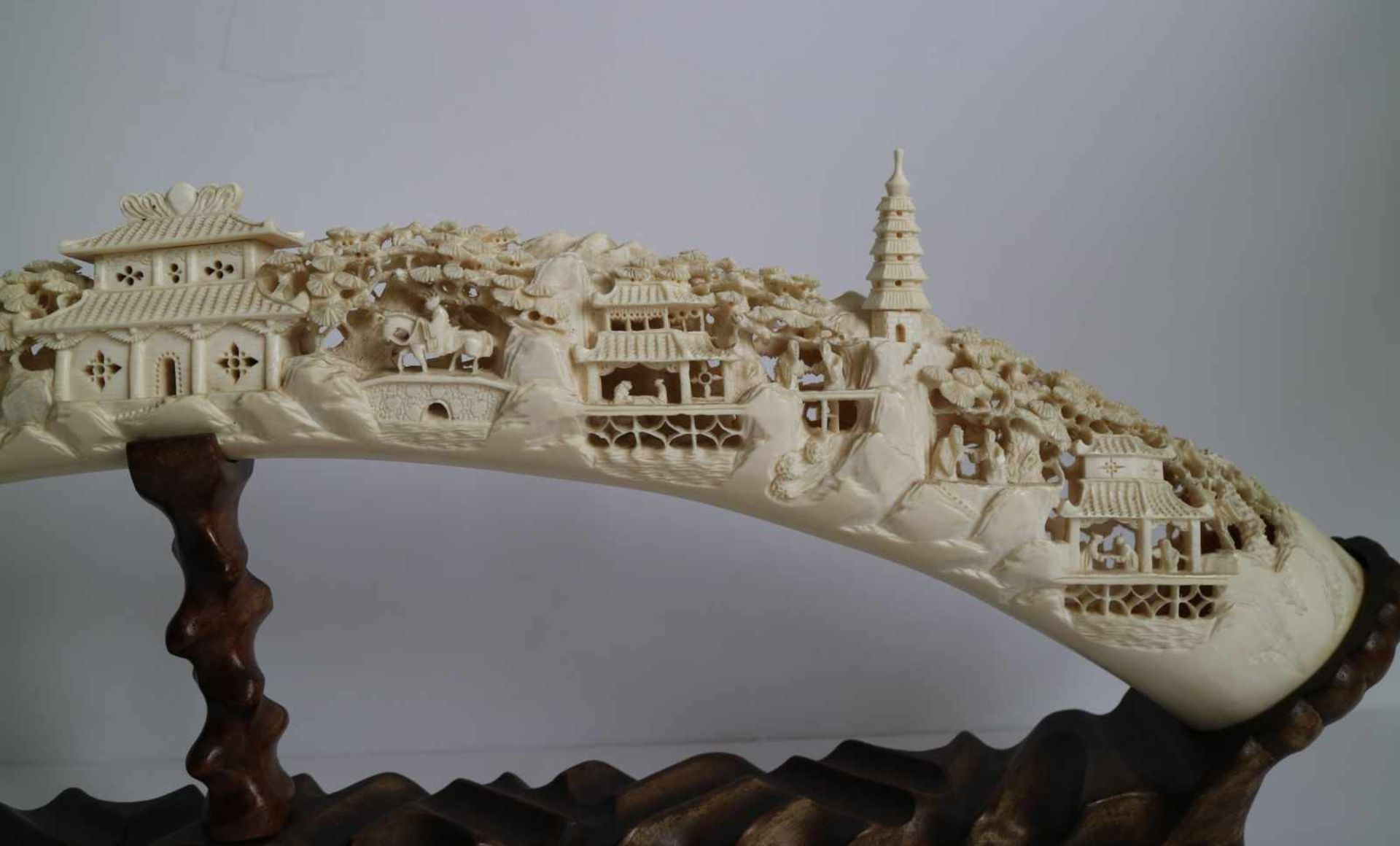 Los 671 - A carved ivory tusk Depicting village scenes with pagodas Canton China ca 1930 L 61 cm