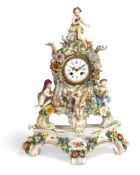 A MEISSEN FLORAL PATTERN PORCELAIN PENDULE AND STAND, c. 1860/80. Rocaille shaped, 4 putti depicting