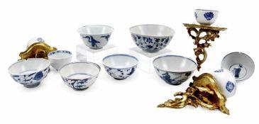 Elf, teils auf Holzsockel montierte, Porzellanschalen mit blau-weißem Dekor