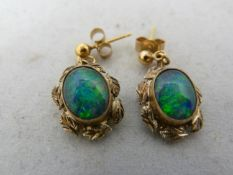 A pair of opal drop earrings, the oval stones set in yellow meal leaf decorated frams on stud drops,
