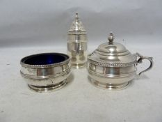 A three piece silver cruet, decorated with beaded and reeded bands beneath vase finials, comprises