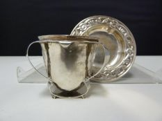 An Arts and Crafts silver egg cup, the plannished body applied with three barbed handles forming a