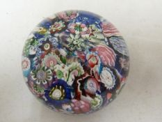 Clichy - a glass paperweight, close packed millifiori canes, 4.5cm diam