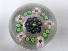 Clichy - a glass paperweight, rose millifiori, the green and pink garland encircling a deep violet
