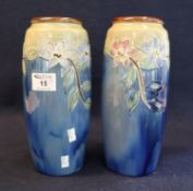 Pair of early 20th Century Royal Doulton stoneware vases decorated on a blue ground with tube