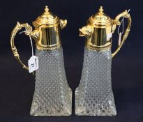 Pair of glass moulded conical claret jugs with gilt metal mounts, covers and foliate loop handles.