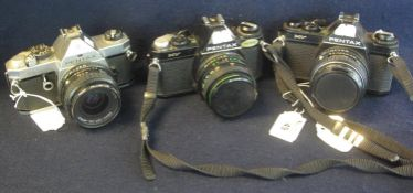 Three Pentax 35mm SLR cameras, MX and two MV models, with Pentax 50mm and 28mm lenses and a