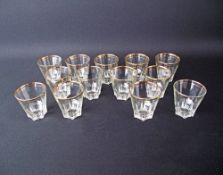 A collection of thirteen vintage pressed glass tumblers H8cm decorated with gilt rims, marked on the