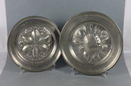 Konvolut Zinnteller2 Stk., Zinn, Reliefteller, davon einer mit Früchterelief, dieser graviert
