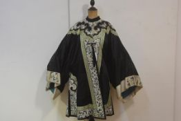 A Chinese silk short robe, c .1900/1920, worked in shades of blue and and green to the applique