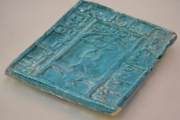 A large turquoise glazed tile, possibly Persian, with moulded decoration of calligraphic type. 35.