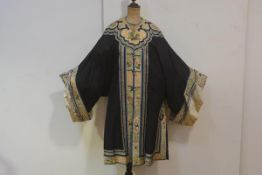 A Chinese silk short robe, c. 1900/1920, worked in polychrome and gilt threads to the collar,