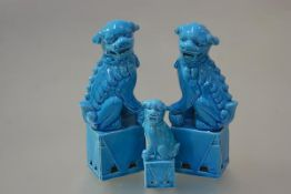 A pair of Chinese turquoise glazed porcelain models of Buddhistic lion dogs, modelled seated, one