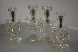 Two pairs of early 19th century cut-glass table lustres, each with crenellated candle cup over a