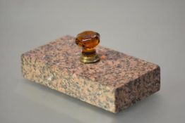 A large 19th century paperweight, in pink granite, the faceted handle in amber glass mounted in