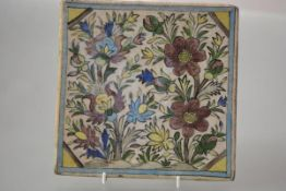 A large Qajar Persian pottery tile, 19th century, polychrome painted with flowers within a turquoise