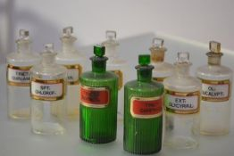 A group of late 19th/early 20th century clear and green glass pharmacy jars: two green, ribbed