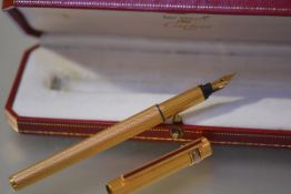 Must de Cartier, a gold-plated fountain pen with engine turned case, faux tortoiseshell clip and