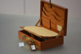 A vintage lady's leather travelling writing case, fitted with writing surface and compartments.