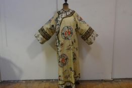 A striking Chinese silk robe, early 20th century, worked in polychrome and gilt threads against a