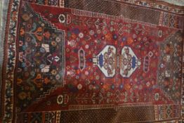 A Persian carpet, the central red field with two geometric urns, flowerhead decoration, flanked by