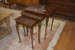 A nest of three walnut coffee table, with scalloped edges, plain friezes, cabriole style legs