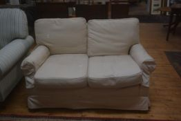 An upholstered two seater sofa with cream loose covers
