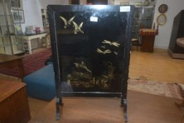 A vintage fire screen with ebonised frame enclosing a panel depicting kingfishers, ducks and