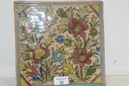 A large Qajar Persian pottery tile, 19thc polychrome painted with flowers and a turquoise border,