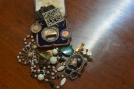 A mixed lot including silver medals and fobs, beads, silver thimble, school badges and brooches