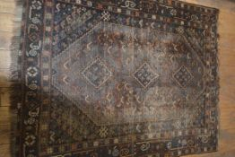 A Turkish carpet, the central field with three diamond shaped medalliions flanked by triple