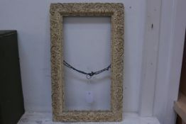 An ornate moulded gilt frame, 27cm x 51.5cm