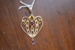 An Art Nouveau pendant with amethyst and seed pearls on yellow metal