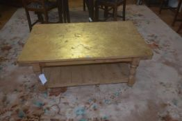 A stripped pine coffee table, the plain rectangular gilded top with plain frieze, block supports,