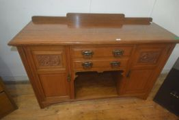An Edwardian oak ledge back sideboard, the rectangular top with moulded edge, two central doors