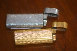 Two Cartier (Paris) Roller gas lighters, one gilt, one white metal (2)