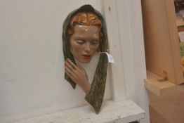 A vintage wall plaque of a woman's head in scarf in painted plaster