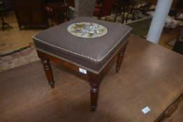 A 19thc mahogany footstool, the upholstered square top with bead work central panel, on plain frieze