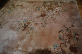 A Chinese wool carpet decorated with urn and floral sprays, with all over floral and leaf