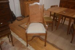 A 19thc colonial style chair, the cane back on shaped arms, upholstered seat, square supports and
