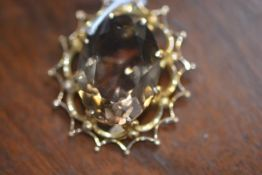 An oval citrine pendant on yellow metal mount