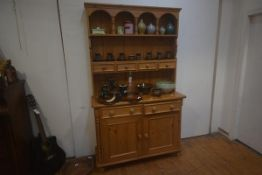 A 19thc two part pine kitchen dresser, the moulded top with arched gallery, a row of four spice