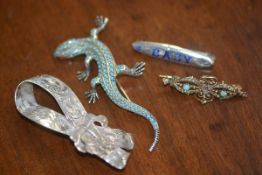 A mixed lot including a white metal bow, a turquoise set gecko, a baby brooch and a yellow metal