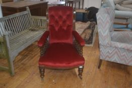A late 19thc upholstered arm chair, the button back with upholstered arms on turned galleried