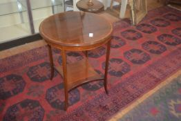 An Edwardian circular rosewood side table, the crossbanded top on square legs with curved ends,